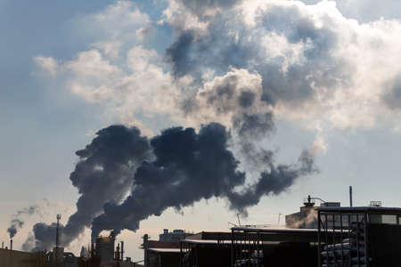 chimney of an industrial company with smoke. symbolic photo for environmental protection and ozone.