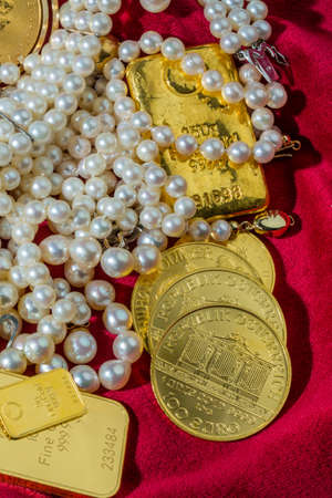 tangible: gold in coins and bars with decorations on red velvet. photo icon for wealth, luxury, wealth tax. Stock Photo