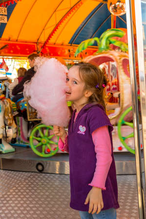 a girl has fun and look at a fairground. and eating cotton candy. Reklamní fotografie