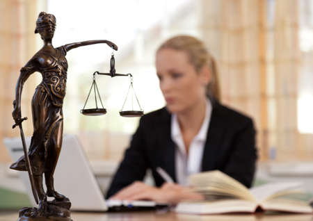 courtroom: a young lawyer is sitting at her desk in the office