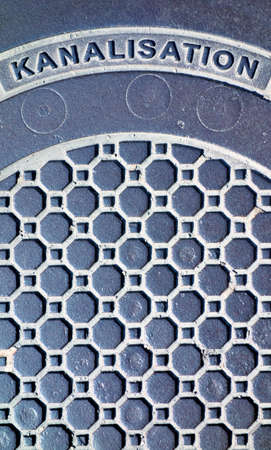 derivation: the cover of a sewer on a street. Stock Photo