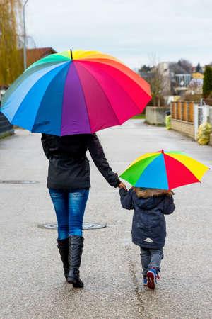 pacto: madre y el niño con el paraguas, un símbolo de solidaridad, ayuda, rescate, rescate Foto de archivo