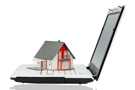 immobilien: house on computertastaur, symbol photo for real estate and housing market on the internet