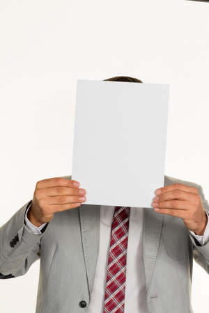 collective bargaining: a young businessman holding a blank sheet over his face. Stock Photo