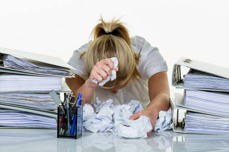 postpone: young woman in office is overwhelmed with work. burnout at work or study.