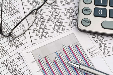examiner: a calculator is located on the numbers a balance us statistics. symbol photo turnover, profits and costs.