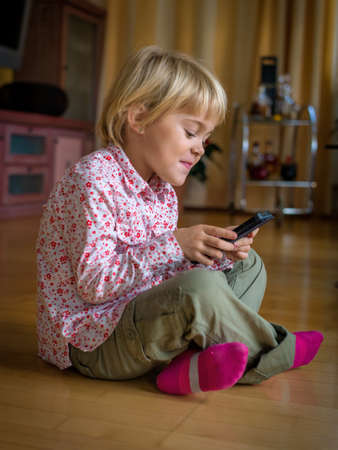 foreign country: a child playing with a cell phone. mobile phone for kids
