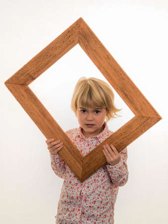 think through: a child holds a frame in her hand and looks through.