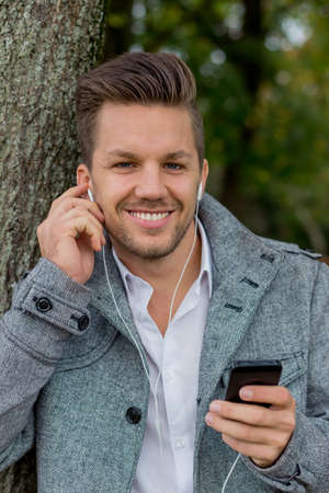 hark: a man listens to music with your phone. talking on the mobile phone. Stock Photo