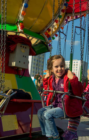 joie: child riding on a fairground with a whirligig and has fun
