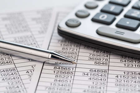 credit report: a calculator is located on the numbers a balance us statistics. photo icon for sales, profit and cost.