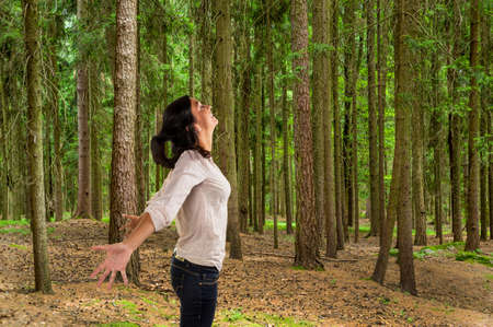 lustful: many trees in a forest with a woman who breathes deeply