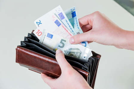 minimum wage: in a purse are some euro banknotes. money is running out by the new poverty.