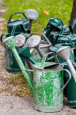 memoirs: watering cans on a cemetery, death, memorial and grave maintenance Stock Photo