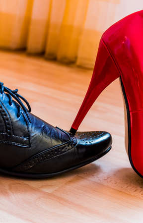 enters: a woman enters a man with her high heels. symbol photo for equality and bullying.