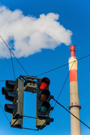 particulate: chimney of an industrial company and a red light. symbolic photo for environmental protection and ozone.