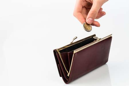 ganancias: una bolsa vacía y una mano que sostiene una moneda delante de un fondo blanco Foto de archivo
