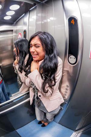 een jonge vrouw met claustrofobie in een lift Stockfoto