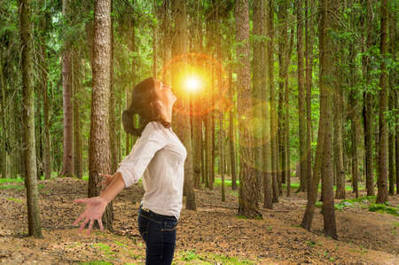 vivre: many trees in a forest with a woman who breathes deeply