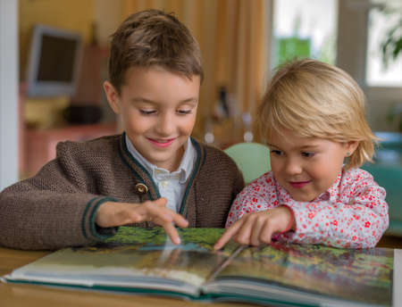 peoplesoft: two children look at a book together on Stock Photo