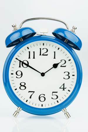 turns of the year: a blue alarm clock on a white background. mikt white dial