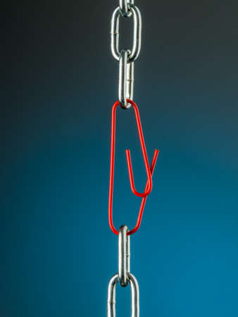 broken trust: a chain is held together with a b?rokklammer. symbol photo for security, trust and teamwork Stock Photo
