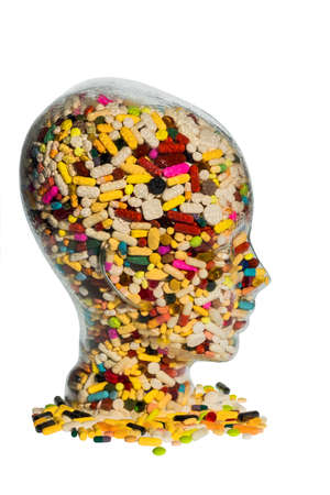 a head made of glass filled with many tablets. symbol photo for drugs abuse and painkillers. 版權商用圖片