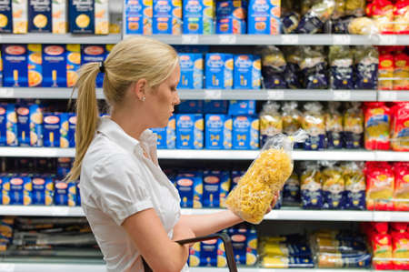 grocers: a young woman shopping with a shopping cart in a supermarket. Stock Photo