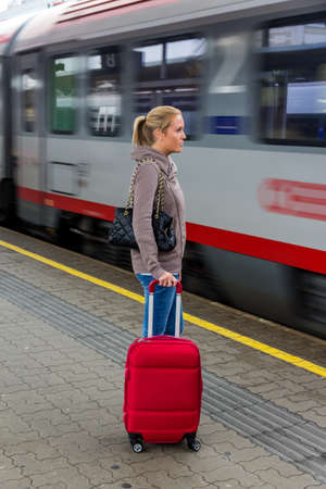 public insurance: a young woman waiting for a train at a station. train holidays