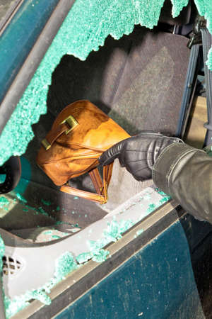 stole: a thief stole a purse from a car through a broken side window. Stock Photo