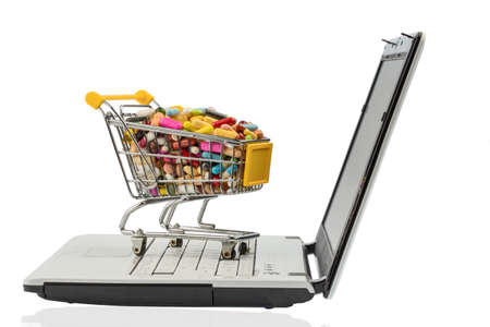 therapie: tablets with shopping cart and computer. symbol photo for the purchase of medicines on the internet Stock Photo