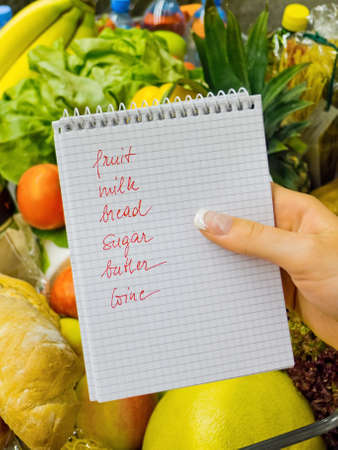 grocers: a woman holding a shopping list in a supermarket in your hands. english language. Stock Photo