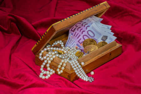 inherit: gold in coins and bars with decorations on red velvet. photo icon for wealth, luxury, wealth tax. Stock Photo