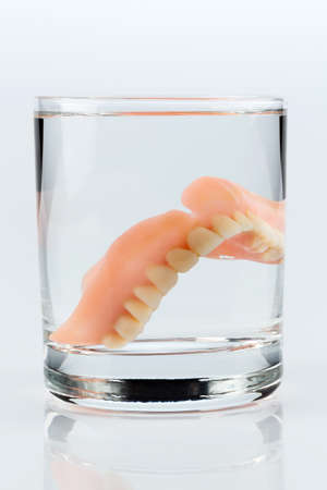 surgery expenses: denture m water glass, symbol photo for dentures and care