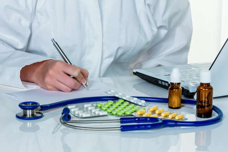 physicans: a young doctor prescribes medication. prescription pills are prescribed by a doctor. Stock Photo