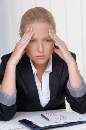 tenseness: a young woman with migraines and headaches sitting in an office. Stock Photo