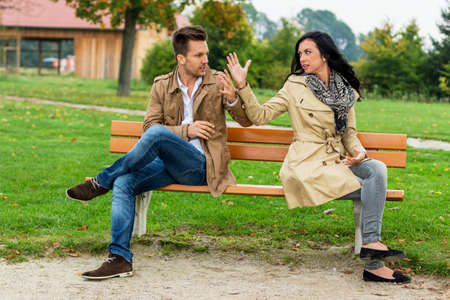 rejection sad: a young couple sitting on a park bench, and fight
