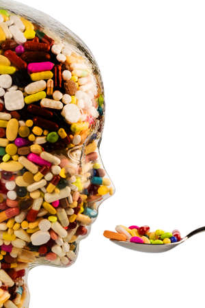 painkillers: a head made of glass filled with many tablets. symbol photo for drugs abuse and painkillers. Stock Photo