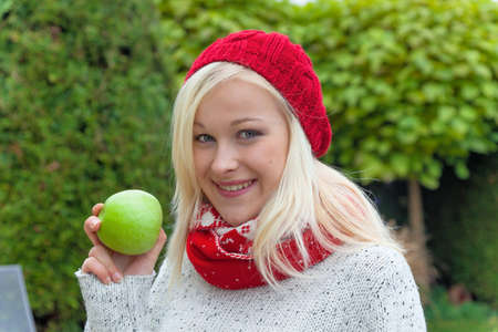 immune system: a young woman with an apple. fruits and vegetables are the right vitamins for a cool fall or winter