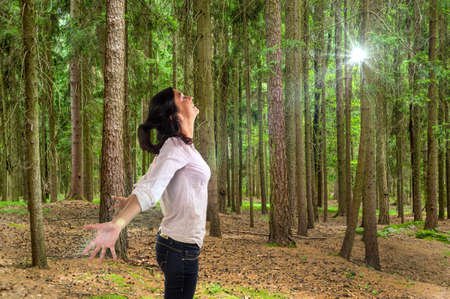 relaxen: many trees in a forest with a woman who breathes deeply