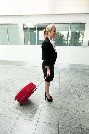 persona viajando: una joven empresaria con la maleta en un aeropuerto. Foto de archivo