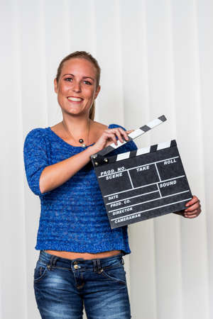 synchronously: a woman holds a typical clapperboard in her hand Stock Photo