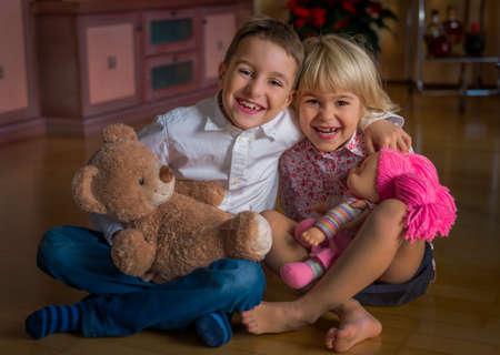 beloved: in a living room sitting siblings and hugging.