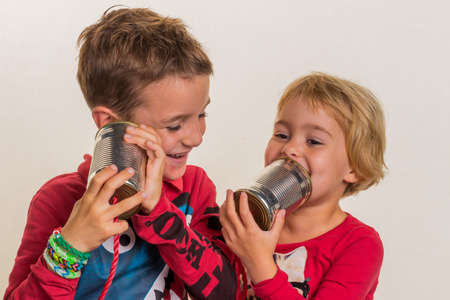 notieren: two little kids calling with a phone of two doses. Stock Photo