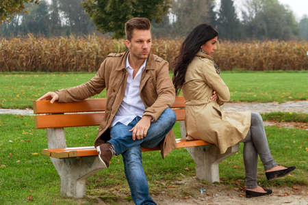 a young couple sitting on a park bench, and fight