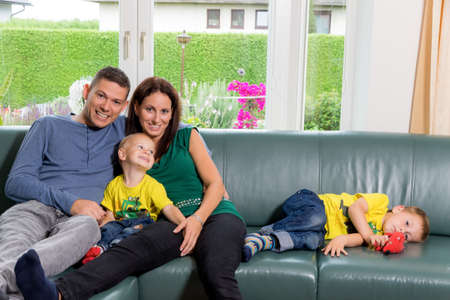 a young family sitting on a couch
