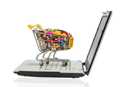 consumerist: tablets with shopping cart and computer. symbol photo for the purchase of medicines on the internet Stock Photo