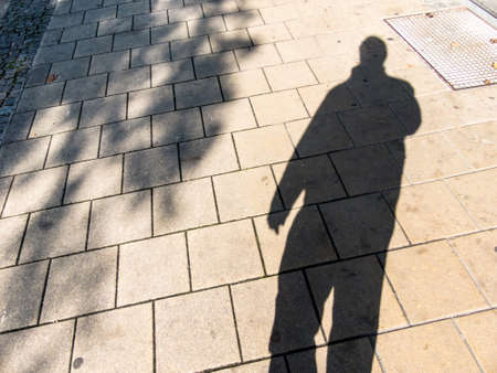 anonymity: the shadow of a man on a sidewalk. anonymity of the big city. Stock Photo