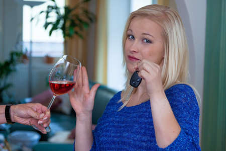 abstinence: a young woman with car keys denied a glass of wine. do not drink and drive Stock Photo