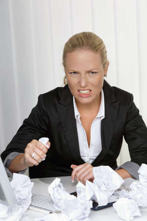 unsuspecting: a woman in the office with paper balls. anger, stress and frustration in the workplace